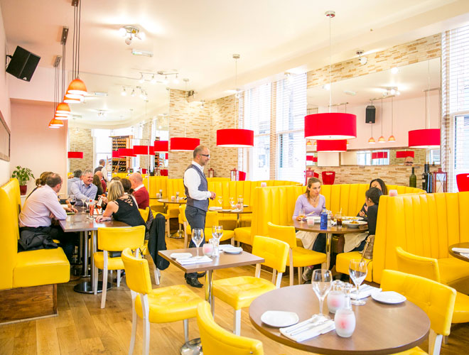 Bright yellow seating and red lamp shades inside La Bandera in Manchester city centre.