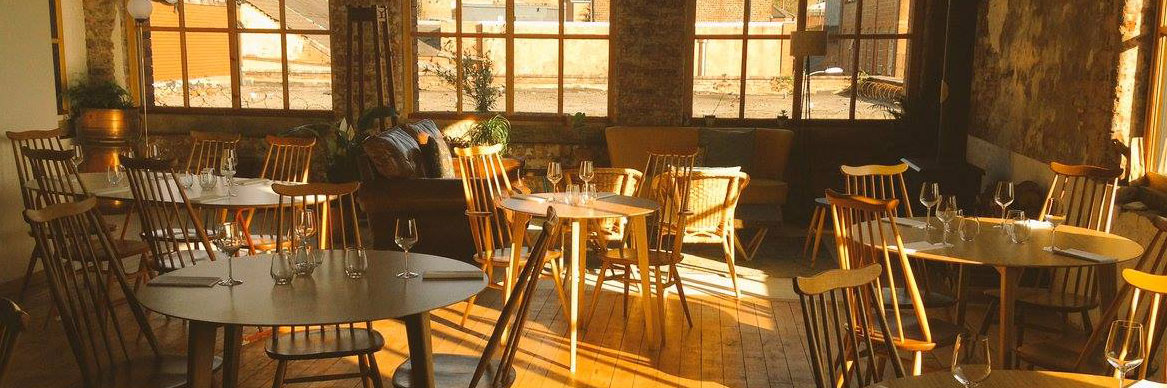 The sun shines through a window onto tables set for dinner at Where the Light Gets In - a recommended restaurant in Stockport