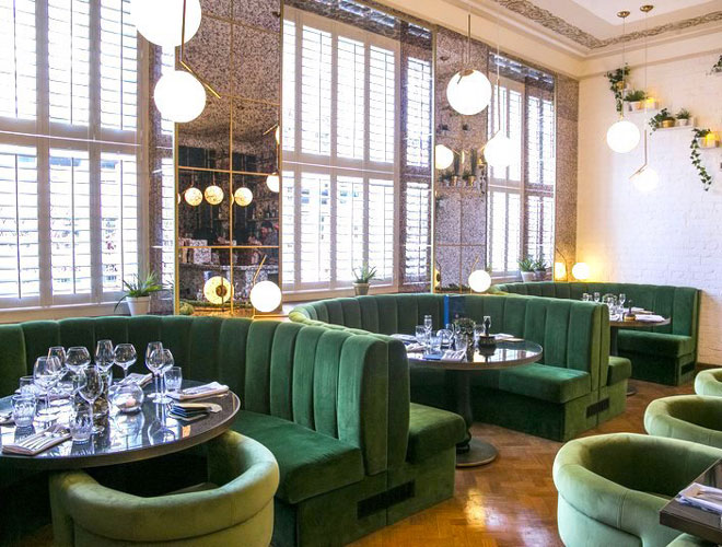 Velvet green booths and natural lighting at Masons Restaurant and Bar in Manchester city centre.
