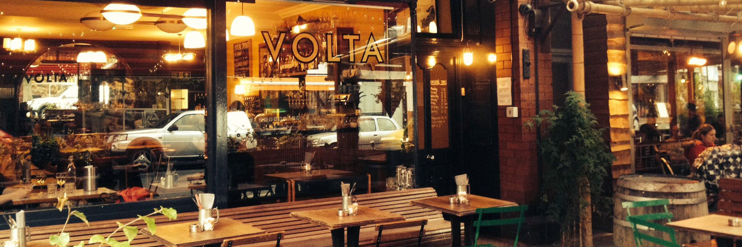 The interior of Volta in Didsbury at night with tables set ready for drinks and dinner