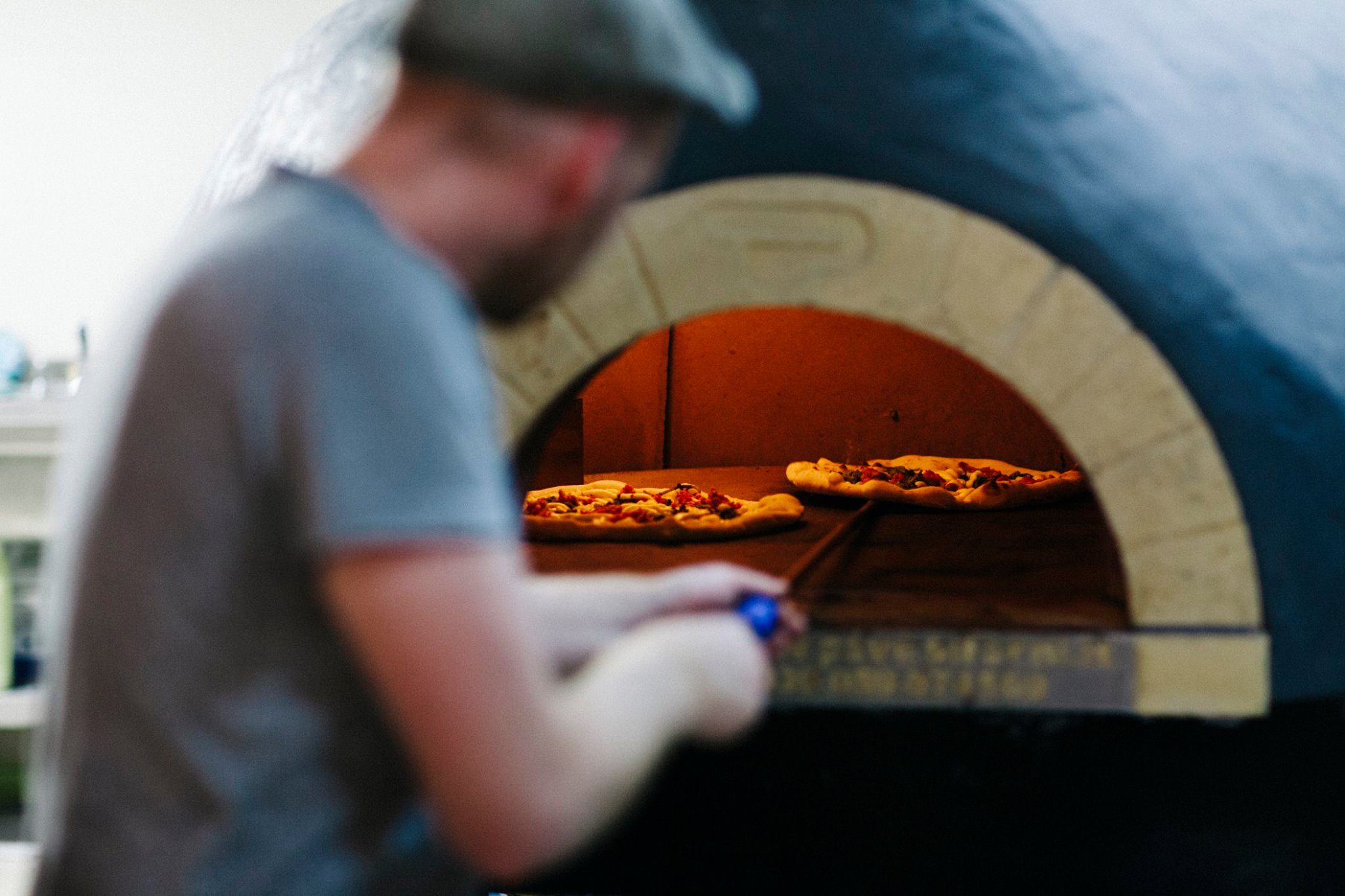 A man cooking Neapolitan pizzas in the wood-fired pizza oven at Rudy's Pizza in Ancoats, Manchester