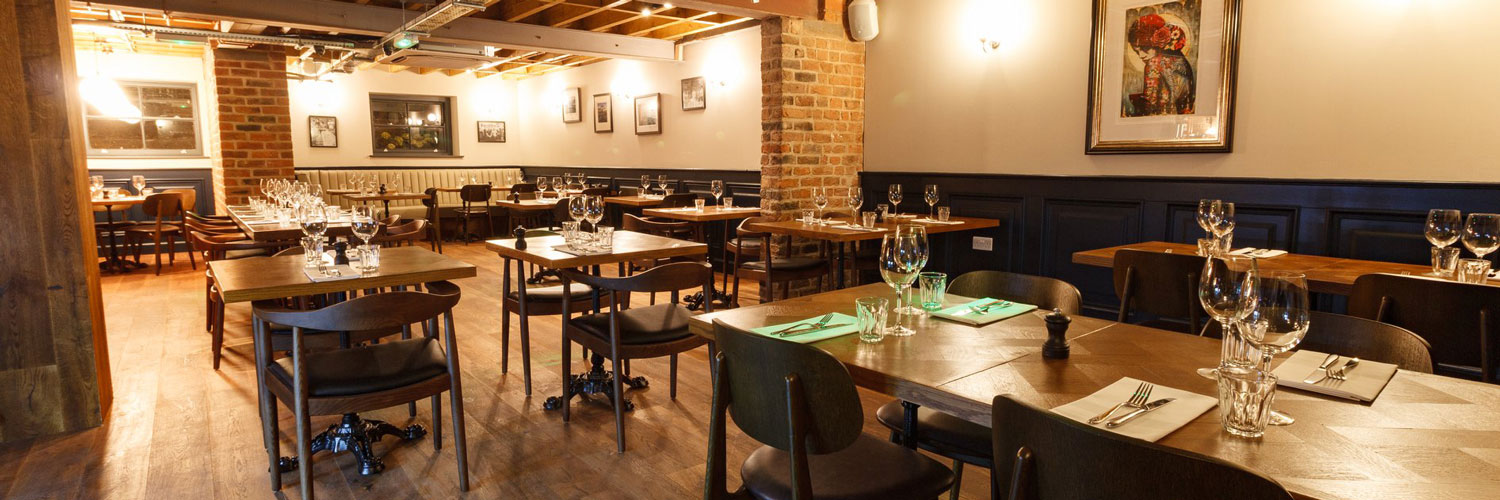 The interior of Wreckfish restaurant in Liverpool city centre with tables set for dinner