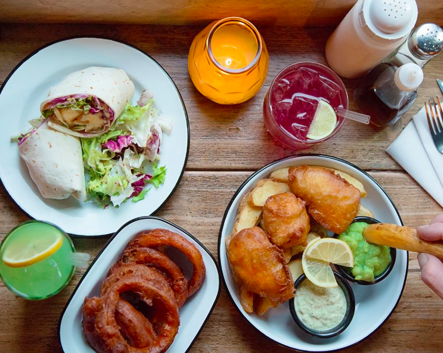 A table laded with drinks and food at Hip Hop Chip Shop in Manchester's Ancoats