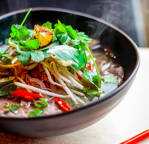 A bowl of pho topped with fresh herbs from Viet Shack Manchester Ancoats, a recommended Vietnamese restaurant