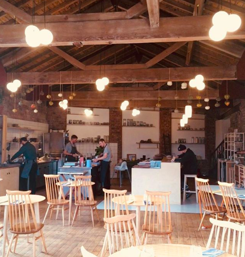 Wooden beams and wooden tables inside Stockport fine-dining restaurant Where the Light Gets In