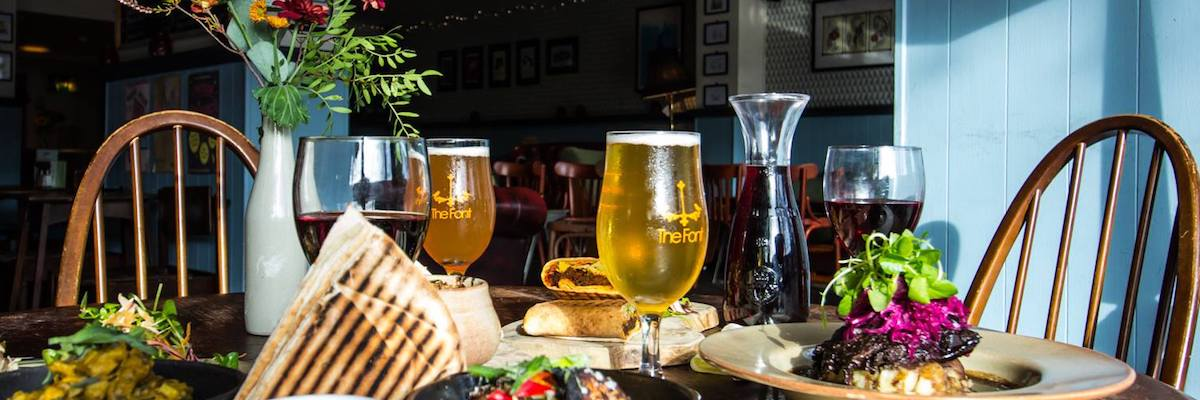 Sunlight falls on a table laden with beers, wine and colourful food at The Font Chorlton