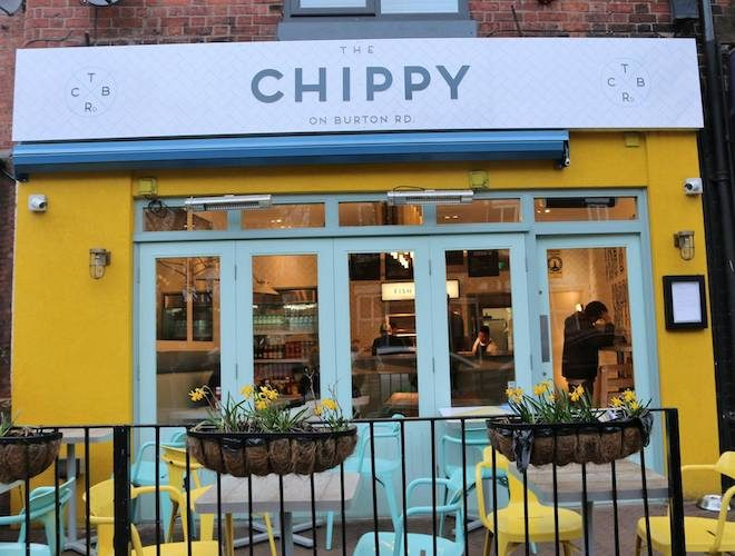 Tables set up outside the bright yellow Chippy on Burton Road - one of the classiest fish and chip shops in Greater Manchester