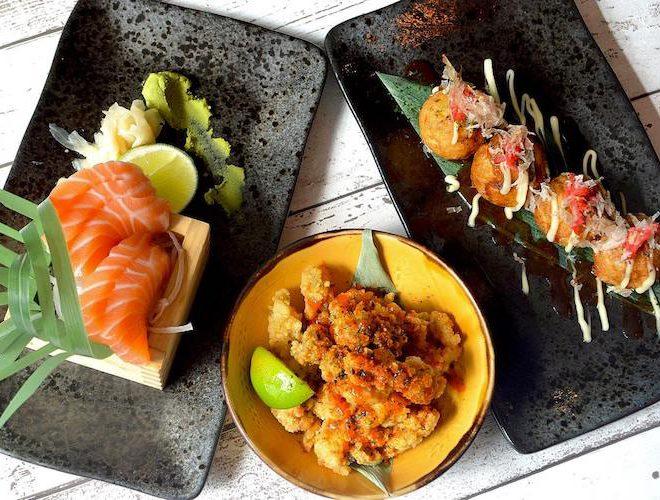 a table of sashimi, takoyaki octopus balls and crispy chilli squid