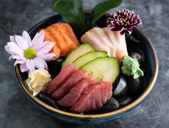 tuna, salmon and yellowtail sashimi in a bowl, served with wasabi and decorated with flowers