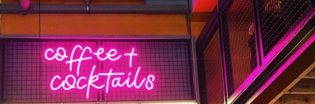 Pink neon sign saying Coffee and Cocktails at Society in Manchester city centre