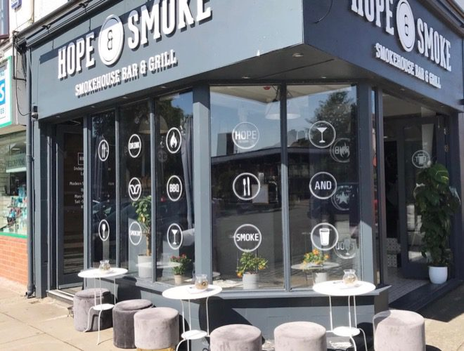 The exterior of Hope & Smoke with seats set out in the sun. This grill restaurant and bar is situated in Allerton, Liverpool.