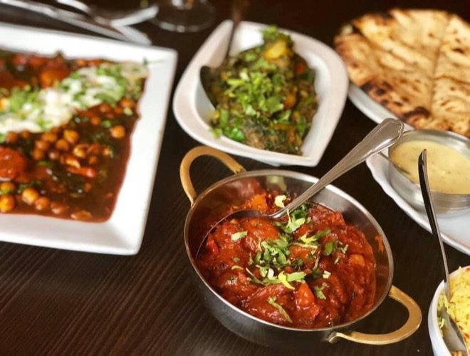 A table laden with dishes at Holdi Woolton - an award-winning Indian restaurant in Merseyside.